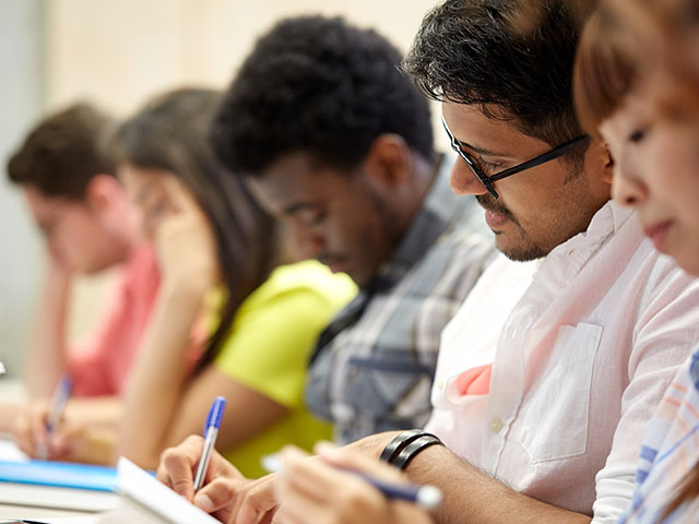 Group of students writing at an event.